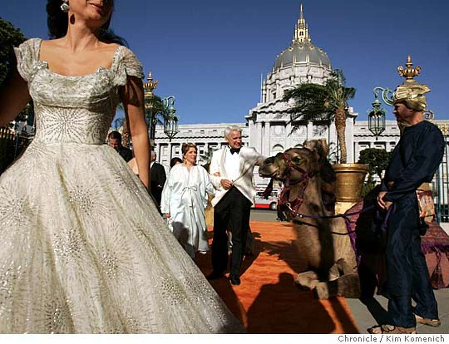 """Woman at left is not identified. Athena and Timothy Blackburn (in white, center) walk the carpet to the opening reception. At right is a camel provided by the opera.  The San Francisco Opera's 83rd opening night gala. NOTE: This shoot (for Bigelow) was done simultaneously with ROSENBURG12 (for Zinko.) We follow operagoers through the parties before the Opera' s performance of """"Italian Girl in Algiers."""" We also shadow outgoing Opera General Director during the hours before the opening.  San Francisco Chronicle Photo by Kim Komenich  9/10/05 Photo: Kim Komenich"""