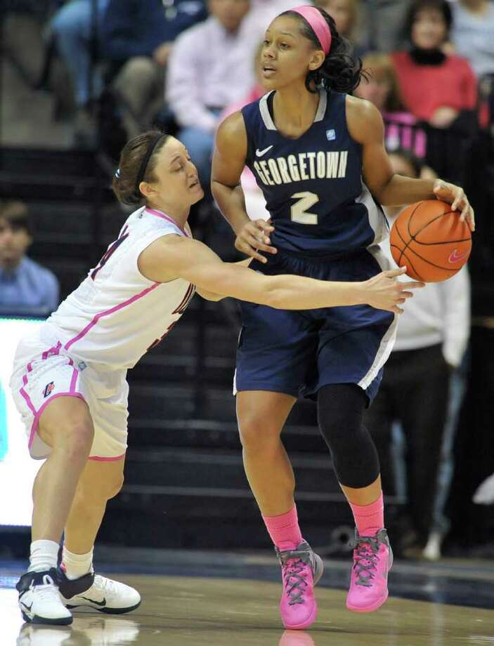 Connecticut's Kelly Faris, left, reaches for the ball around Georgetown's Tia Magee's during the first half of an NCAA college basketball game in Storrs, Conn., Saturday, Feb. 11, 2012. (AP Photo/Jessica Hill) Photo: Jessica Hill, Associated Press / AP2012