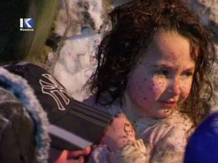 In this image made from Klan Kosova TV video, rescuers carry a 5-year-old girl pulled alive from the rubble of a house flattened by a massive avalanche that killed both of her parents and at least seven of her relatives in the remote mountain village of Restelica, southern Kosovo, Sunday, Feb. 12, 2012. Col. Shemsi Syla, a spokesman for the Kosovo Security Force, said the girl was discovered in the ruins, buried under 10 meters (33 feet) of snow, when officers heard her voice and the ringing of a cell phone. (AP Photo/Klan Kosova TV) KOSOVO OUT, TV OUT / Klan Kosova TV