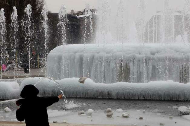 A boy throws a piece of ice into a frozen fountain in Milan, Italy, as a cold front continues to affect the country, Sunday, Feb. 12, 2012. (AP Photo/Luca Bruno) Photo: Luca Bruno / AP