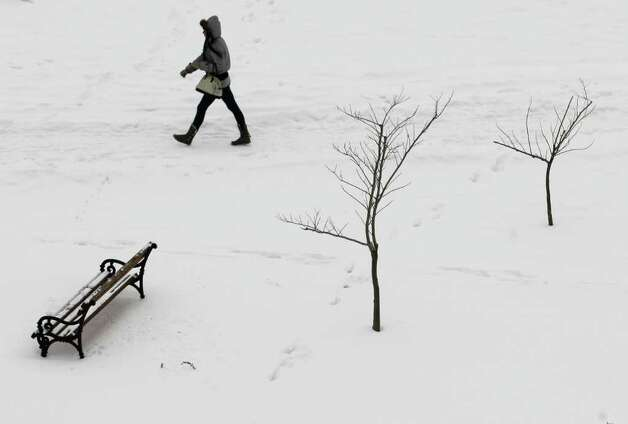 A woman walks through a snow-covered park in Nis, Serbia, Sunday, Feb. 12, 2012.  Serbia is struggling to maintain its power system amid record low temperatures in the Balkan country and much of Europe. (AP Photo/Darko Vojinovic) Photo: Darko Vojinovic / AP