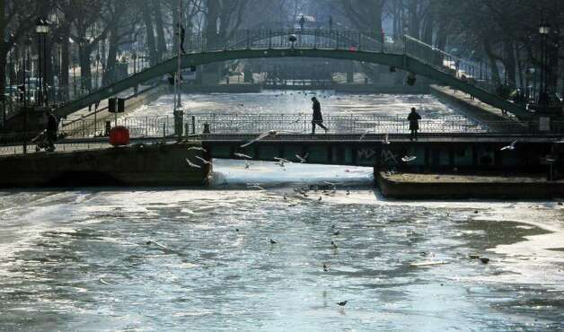 People cross a bridge over the frozen Canal Saint-Martin in Paris, Sunday, Feb. 12, 2012. A cold snap in Europe, which began in late January, has killed hundreds of people - most of them homeless, as below-freezing temperatures persist. (AP Photo/Tony Hicks) Photo: Tony Hicks / AP