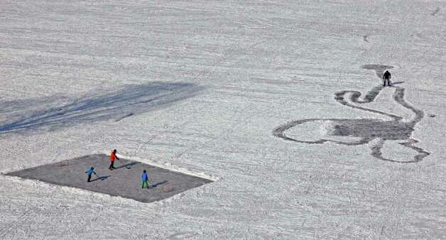 People enjoy the sun on a frozen lake in the Olympic park in Munich, southern Germany, Sunday, Feb. 12, 2012. Europe has been battling a deep freeze that started in late January. (AP Photo/Matthias Schrader) Photo: Matthias Schrader