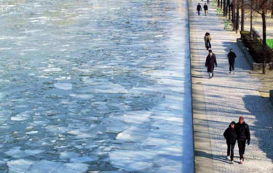 People walk alongside the frozen Canal de la Villette in Paris, Sunday, Feb. 12, 2012. A cold snap i
