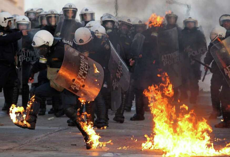 A riot police officers tries to extinguish flames from a petrol bomb thrown by protestors outside th