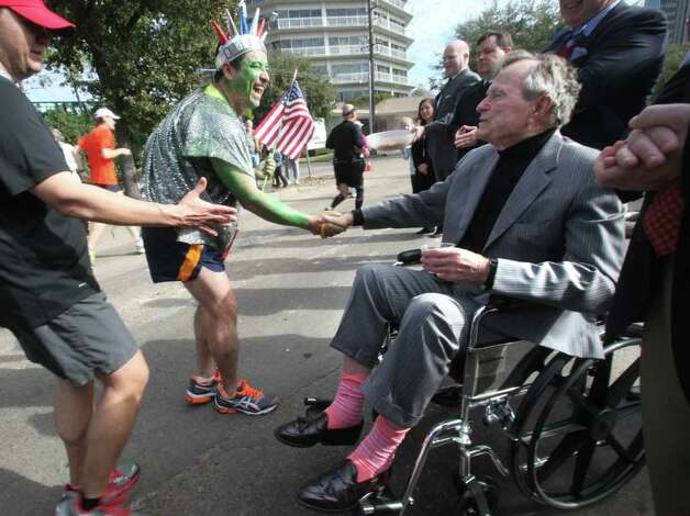 The former president's bright pair of socks may have prompted a few double takes at January's Chevron Houston Marathon. Antonio Lopez-Perla stopped to shake hands. Photo: Mayra Beltran / © 2011 Houston Chronicle