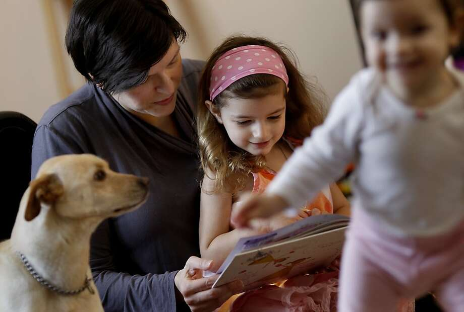 Marija Maldonado reads to her daughter Ivana in the living room of their home while daughter Elida (right) and the family dog Apollo mess around. Marija Maldonado, a mother of three girls in San Francisco, Calif., is upset because her daughter Ivana was denied acceptance to kindergarten because she was born one day late according to the school district rules.  Maldonado would accept transitional kindergarten for her daughter but now the district has cancelled that option. Photo: Brant Ward, The Chronicle