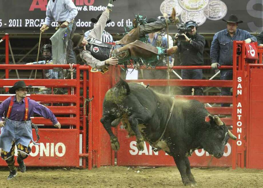 Seth Glause of Cheyenne, Wyo., flies off a bull Sunday, Feb. 12, 2012 during the bull riding competition at the San Antonio Stock Show & Rodeo. Photo: John Davenport, San Antonio Express-News