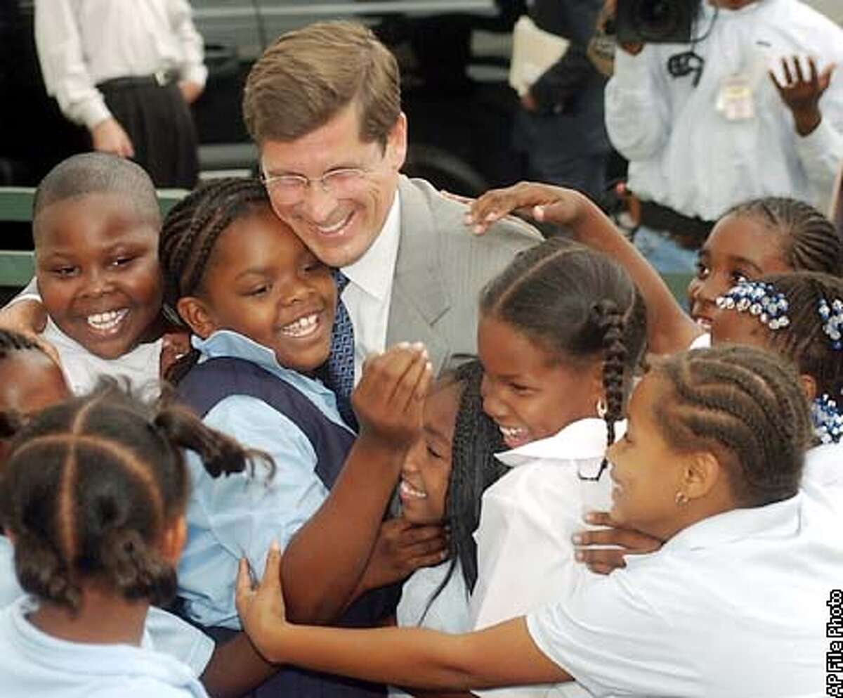 ** CORRECTS DATE TO SEPT. 5, NOT AUG. 5 ** Republican gubernatorial candidate Bill Simon, in suit, is greeted by children at the Watts Learning Center in Los Angeles, Thursday, Sept. 5, 2002. Simon visited the Los Angeles Unified charter school to discuss education policy. He is to face California Gov. Gray Davis, a Democrat, in the November general election. (AP Photo/John Hayes)