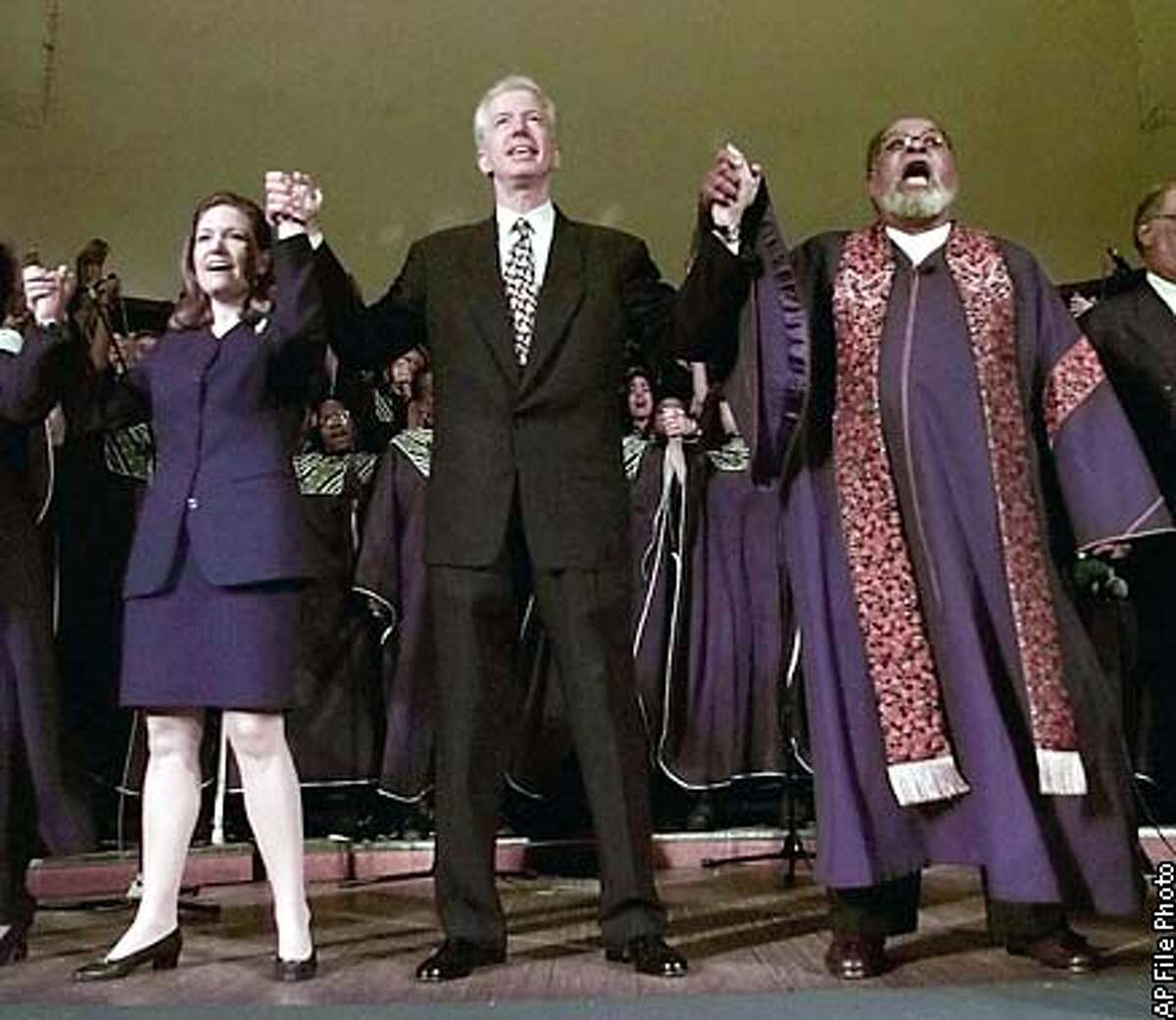 """Democratic candidate for governor, Gray Davis, center, joins hands with his wife, Sharon Davis, left, and Rev. Cecil Williams, right, as they sing """"We Shall Overcome"""" at the Glide Memorial Church in San Francisco, Sunday, May 24, 1998. Willams announced his retirement from the church earlier in the week. (AP Photo/Paul Sakuma)"""