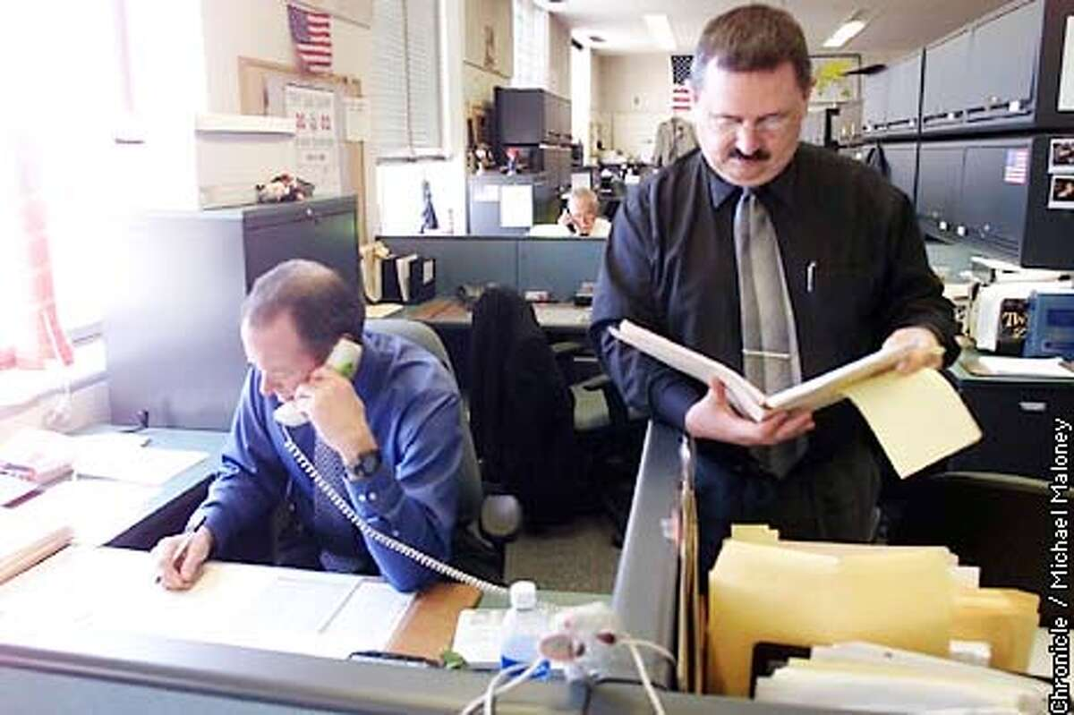 COPS1-C-13MAR02-MT-MJM SFPD General Work's Lt Henry Hunter (right) looks over a case report near the desk of Inspecter Steve Venters (seated, left). Both work for General Work which handles the initial calls including violent crimes. CHRONICLE PHOTO BY MICHAEL MALONEY