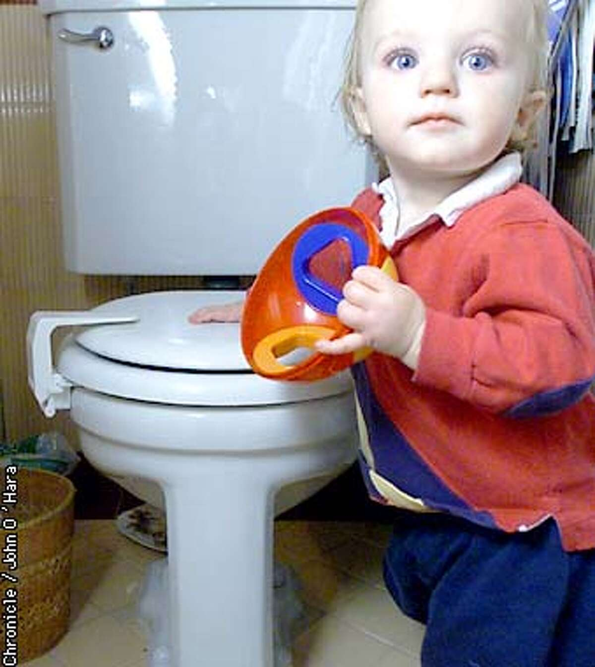 """San Francisco,CA """"Harry"""" , standing next to the childproof comode lock. A Toliet lid lock, sells for $10.99. Photo/John O'Hara"""