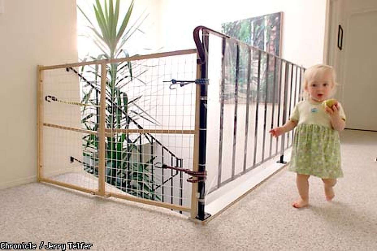 Sophia Krivoruchko (18 months) goes about her activity, protected by a stairway gate and heavy plastic sheeting along the rail to prevent falls. Parents Margaret and Nick Krivoruchko have added childproofing to their Mill Valley, CA home to avoid accidents for Sophia and her brother Misha (4). 807 Spring Drive - Mill Valley, CA CHRONICLE STAFF PHOTO BY JERRY TELFER