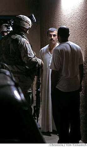IRAQ07_RAID_0118_KK.JPG  Soldiers interview a resident as the rest of his family is allowed to come back into their home a search for insurgents and bomb-builders, soldiers from Steel Company, 2nd Battalion, 7th Infantry Regiment, 1st Brigade,Third Infantry Division, US Army raid homes and search neighborhoods in Wynot, a town near Tikrit, Iraq.  San Francisco Chronicle Photo by Kim Komenich  10/6/05 Ran on: 10-09-2005  While his family waits nearby, an Iraqi man extends his arms as he undergoes a search at a checkpoint near al Ubaydi. The U.S. military has been cracking down on insurgent activity near the Syrian border. Photo: Kim Komenich