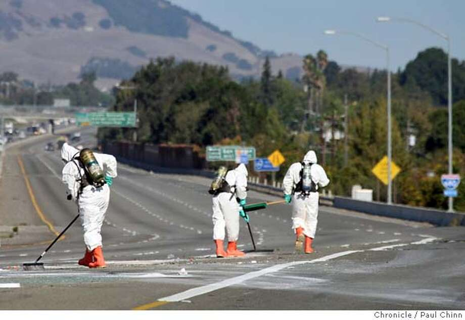 A hazardous materials crew from Alameda County cleans up pool chemicals dumped by a pickup truck that overturned at the Interstate 580 and 680 interchange in Dublin, Calif. on Wednesday, Oct. 3, 2007. The accident forced the closure of all lanes of northbound I-680 for several hours. It was the second major freeway accident in the Livermore Valley choking an already crowded morning commute. PAUL CHINN/The Chronicle Photo: PAUL CHINN