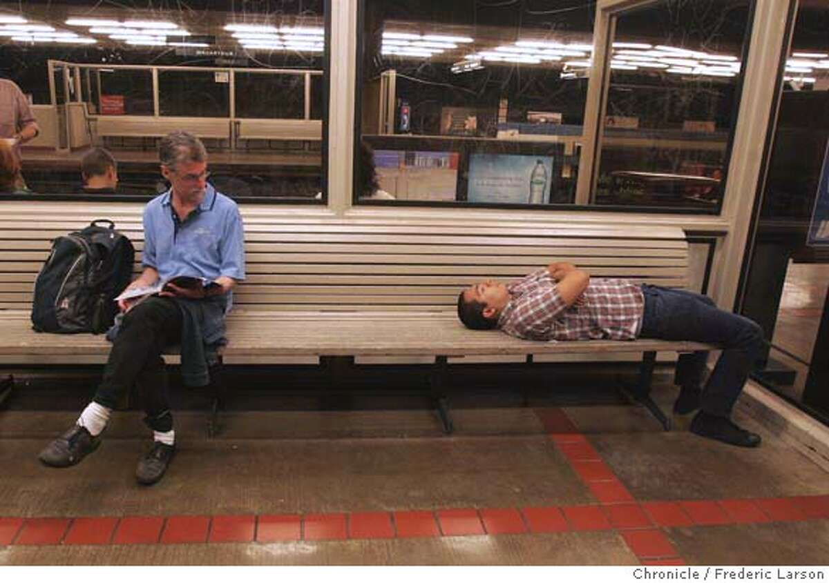 Paul Wilcox Baker (left) reads as another passenger was napping while waiting for a late night/early morning Bart train at the MacArthur Street Station at 2 AM in Oakland. While workers raced to fill a gaping 350-foot hole they had demolished in middle of the Bay Bridge's upper deck Monday morning, Bay Area drivers avoided the chaos that might have come with the holiday-weekend closure of the region's key viaduct by staying off the roads in droves and taking BART. BART ran trains all night on Labor Day morning as when it is usually closed. Late night party goes packed the Powell Street station after last call and enjoyed safe ride to the east bay many feeling no pain at all from the inconvenience of the bridge being closed. 9/3/07 {Photographed by Frederic Larson} MANDATORY CREDIT FOR PHOTOGRAPHER AND SAN FRANCISCO CHRONICLE/NO SALES-MAGS OUT