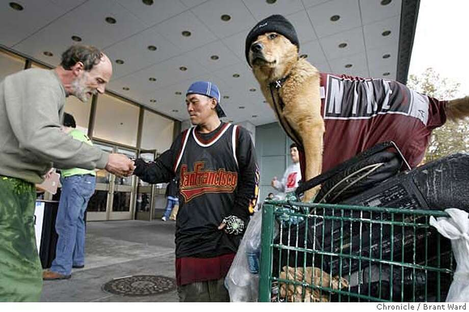 A man identified only as Michael (center) is helped by an unidentified man as Belle keeps watch over Michael's belongings at Project Homeless Connect at the Bill Graham Auditorium in San Francisco. Chronicle photo by Brant Ward