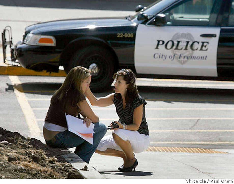 Sue McGaughey (right) comforts her daughter Ashley who was upset after seeing blood stains after two students were stabbed during school hours at John F. Kennedy High School in Fremont, Calif. on Wednesday, September 20, 2006. The school remained in lock down mode for several hours while police investigated at the scene.  PAUL CHINN/The Chronicle  **Sue McGaughey, Ashley McGaughey Photo: PAUL CHINN