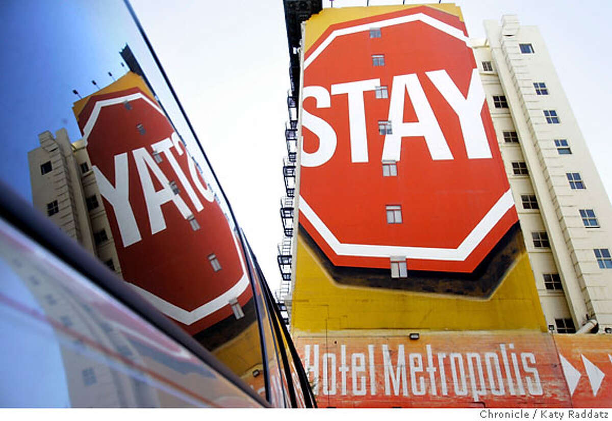 """HOTELS_METROPOLIS_053_RAD.jpg SHOWN: The side of the hotel seen from Mason St. The big """"Stay"""" sign is reflected in the window of a guest's Jeep Cherokee in the secure parking lot. The Metropolis Hotel, 25 Mason St. and 16 Turk St. in San Francisco. These photos were made on Wednesday, Oct. 18 2006, in San Francisco, CA. (Katy Raddatz/San Francisco Chronicle) **Metropolis Hotel Ran on: 11-09-2006 The side of Hotel Metropolis from Mason Street, above left. Each floor of the hotel has a different theme, such as this 10th-floor wind room, right. Below, the bathrooms are basic: large, white with accent tiles. But you do get a welcome kit that includes toiletries. Ran on: 11-09-2006"""