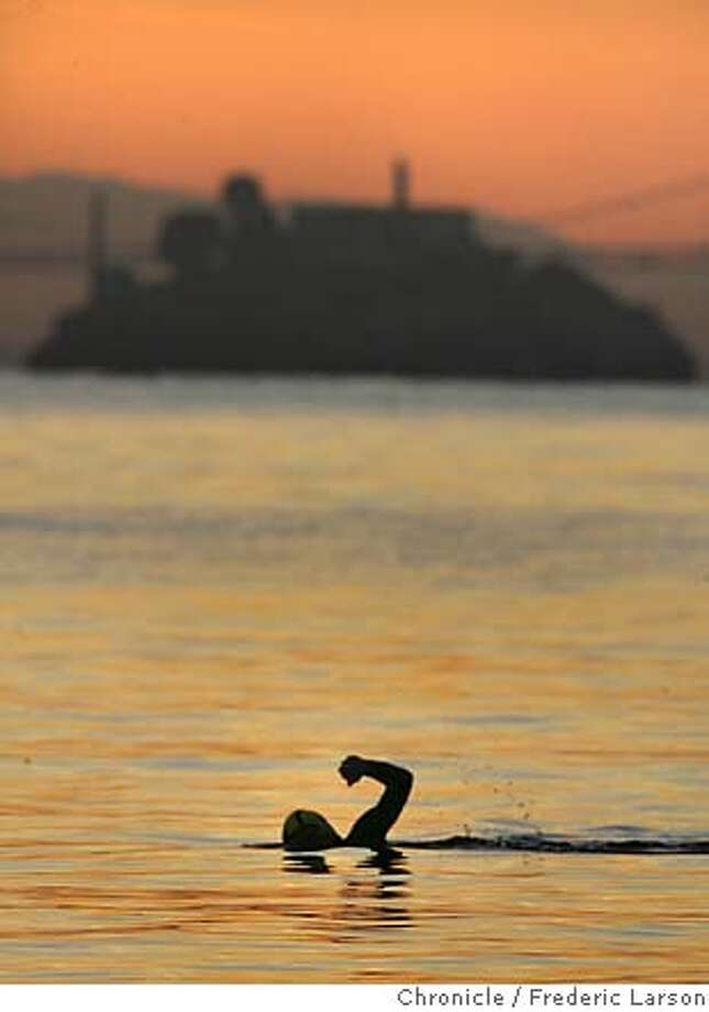 One brave soul just before sunrise who obivously doesn't mind the chilly San Francisco Bay took a swim off the shores of Sausalito with Alcatraz Island as his back-drop 11/10.  11/10/06  {Photographed by Frederic Larson} Photo: Frederic Larson