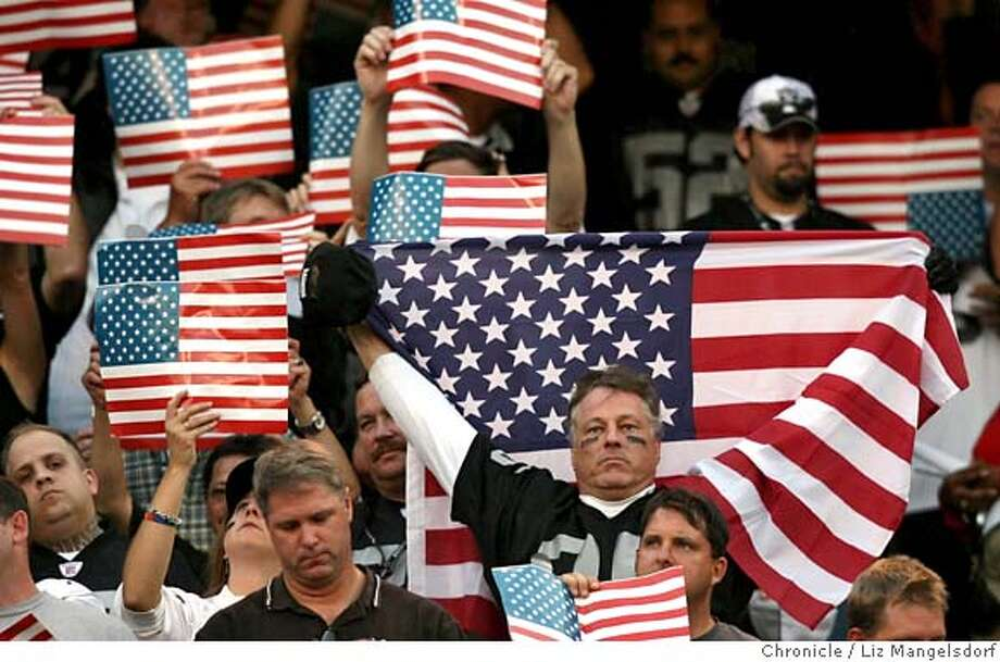 Fans hold up flags during the pregame ceremony honoring victims of 9-11 on the 5 year anniversary.  Oakland Raiders play the San Diego Chargers at McAfee Coliseum on Sept. 11, 2006.  Liz Mangelsdorf /The Chronicle Photo: Liz Mangelsdorf