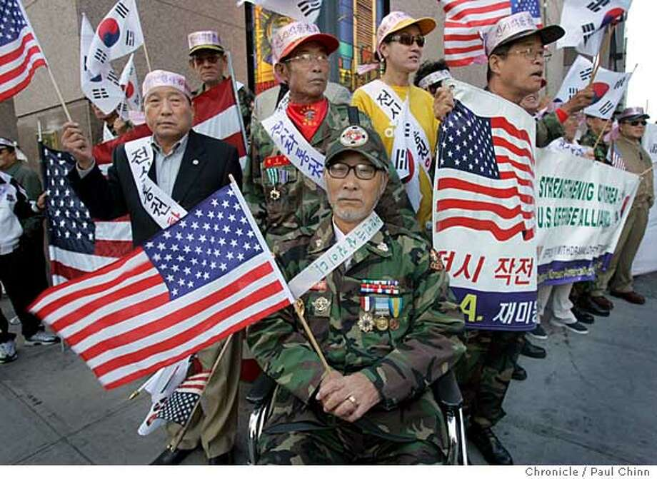 Young Sooyoo (center) and other Korean War vets demonstrated across from the Hotel Nikko where South Korea president Roh Moo-hyun met with Bay Area dignitaries at a conference at in San Francisco, Calif. on Friday, September 15, 2006. The veterans group is seeking a stronger alliance between the U.S. and South Korean governments.  PAUL CHINN/The Chronicle  **Young Sooyoo, Roh Moo-hyun Photo: PAUL CHINN
