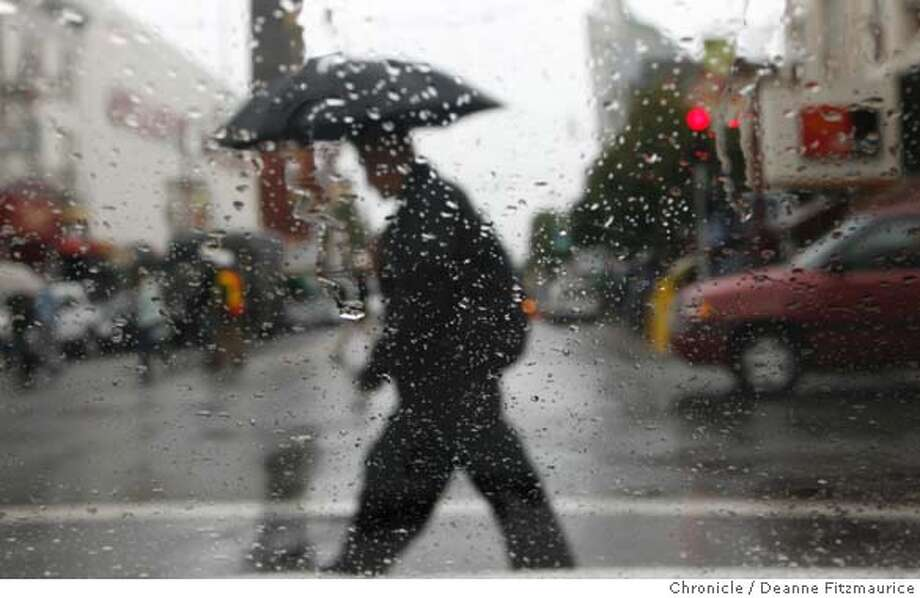weather_0143_df.jpg  A man crosses Mission Street, as seen through a wet windshield, with an umbrella in the first big rainfall of the season. Event in San Francisco on 11/2/06. (Deanne Fitzmaurice/ The Chronicle) Mandatory credit for photographer and San Francisco Chronicle. /Magazines out. Photo: Deanne Fitzmaurice