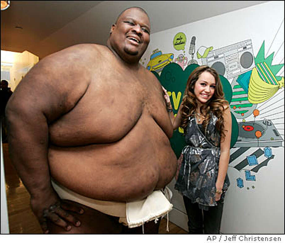 Miley Cyrus appears back stage with sumo wrestler Manny Yarbrough during MTV's 'Total Request Live' show at the MTV Times Square Studios, Monday, Oct. 23, 2006, in New York. Photo: JEFF CHRISTENSEN