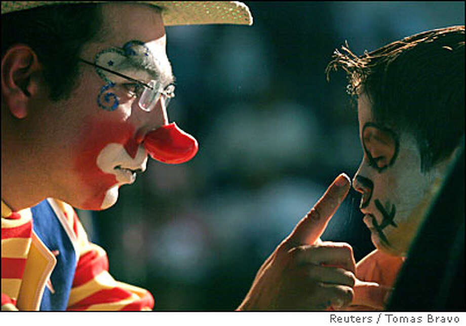 A boy has his face painted by a clown during the International Clown Convention in Mexico City Photo: TOMAS BRAVO