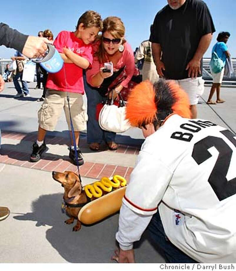 """doggies_0002_db.JPG  Cele Glover, 15, right, and Mom, Mitsuno Baurmeister, left with leash, hold """"Angel,"""" a 5-year-old, female, miniature dachshund, dressed as a hot dog, as Dylan, 8, and parents Michelle and Frank Martinez, back, all fro Fresno, watch, as they wait to participate in the 10th Annual Dog Days of Summer, presented by Wag Pet Hotels and Purina, in which many dogs join in some pre-game festivities including a costume contest, as well as receive a goody bag and leash at AT&T Park prior to the Giants vs. Colorado game at San Francisco, CA on Saturday, August 5, 2006. 8/5/06  Darryl Bush / The Chronicle ** Cele Glover, Mitsuno Baurmeister , Frank & Michelle Martinez, Dylan Martinez, (cq) MANDATORY CREDIT FOR PHOTOG AND SF CHRONICLE/ -MAGS OUT Photo: Darryl Bush"""