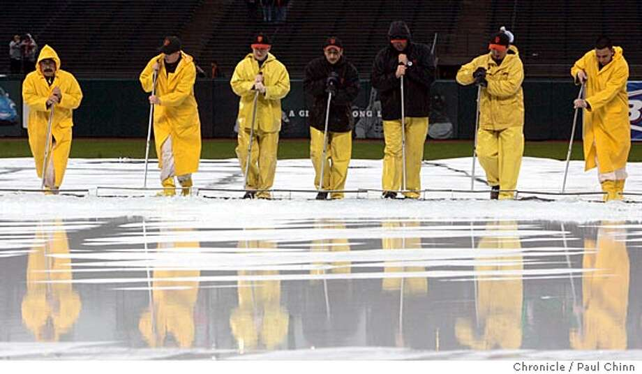 Groundskeepers remove rain water from the tarp which has delayed the start of Friday's game. The San Francisco Giants vs. the Atlanta Braves at AT&T Park on 4/7/06 in San Francisco, CA.  PAUL CHINN/The ChronicleRan on: 04-08-2006  Groundskeepers remove rainwater from a tarp covering the infield at AT&T Park, where a game between the Giants and the Atlanta Braves was delayed more than an hour and a half in the first inning. More rain, and perhaps baseball, is expected through the weekend. Photo: PAUL CHINN