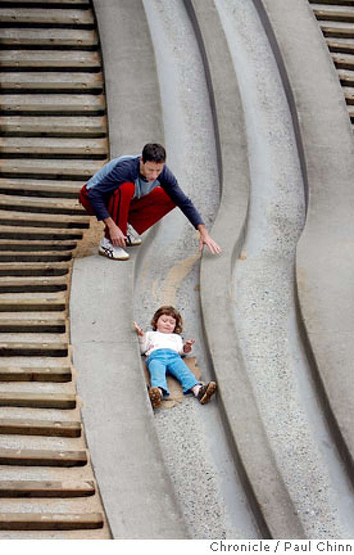 Gil Heiman helps his daughter Ines, 3, slip down the concrete slide at the Children's Playground which reopened at Golden Gate Park in San Francisco, Calif. on Saturday, July 14, 2007. The $3.8 million renovation project on the playground, that originally opened in 1887, took a year-and-a-half to complete. PAUL CHINN/The Chronicle ***Gil Heiman, Ines Heiman