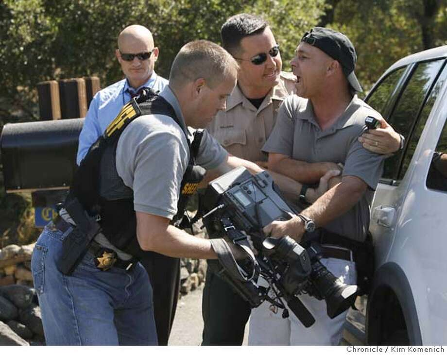 Napa County Sheriffs deputies detain KGO-7 photographer Craig Southern after he was attempting to get video of firefighters battlinga vegetation fire off Atlas Peak Road near the Silverado Country Club Wednesday. KGO reporter Wayne Freedman, who was also arrested, is in the background.  Photo by Kim Komenich/The Chronicle  **Craig Southern, Wayne Freedman Photo: Kim Komenich