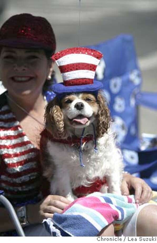 Petunia sits on Denise Enos' lap as they watch the parade pass by on Park Street.  City of Alameda Mayor's Fourth of July Parade on July 4th, 2007. Photo taken on 070407 in Alameda, CA.  Photo by Lea Suzuki/ The Chronicle  ()cq Photo: Lea Suzuki