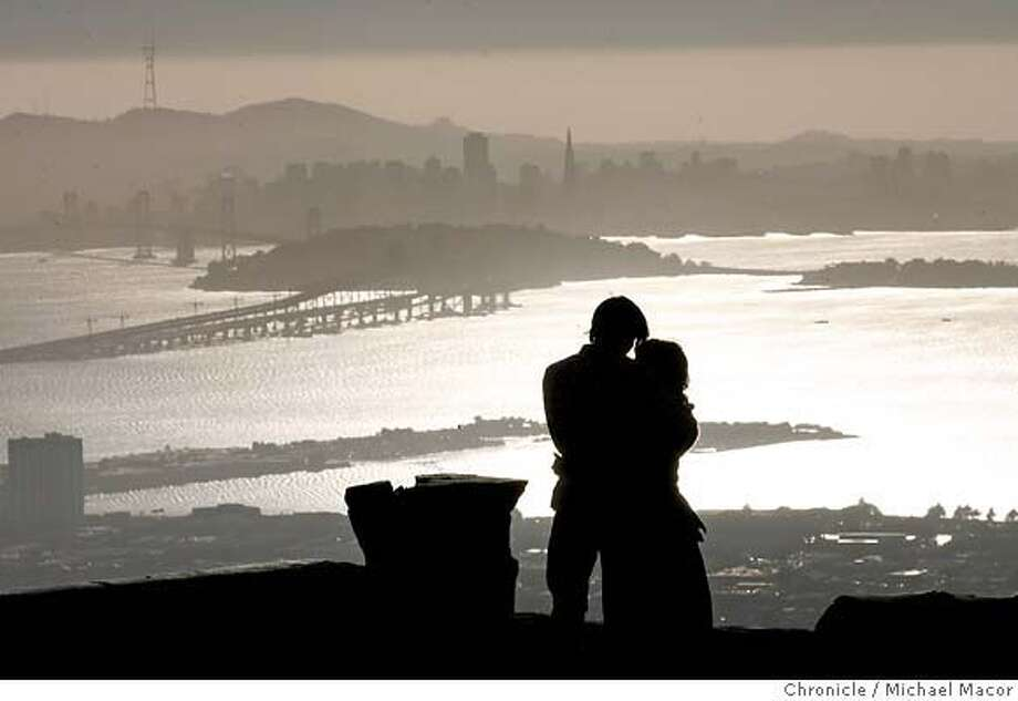 Happy Valentine's Day, Dennis Remsing and Loreto Marin enjoy the beautiful view of San Francisco as well as each other. They plan to wed later this year. From the Oakland HIlls along Grizzly Peak Rd. people enjoy the late afternoon sun as it begins it final hours.Event in Oakland, Ca on 2/15/06 Photo by : Michael Macor/ San Francisco Chronicle Photo: Michael Macor