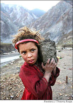 A Kashmiri refugee girl carries a stone to help her father build a wall in the Neelum Valley near Kamsar camp, some 10 km (6 miles) north of the earthquake-devastated city of Muzaffarabad in Pakistan-administered Kashmir February 15, 2006. Winter weather has made life more difficult for survivors of last year's massive earthquake in South Asia, where more than two million people have been living in tents or crude shelters patched together from ruined homes. REUTERS/Thierry Roge Photo: THIERRY ROGE