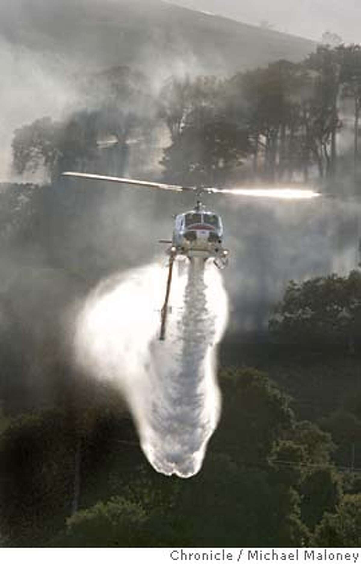 A Cal Fire Helicopter drops water on a fire in the hills near Stanford. Helicopters dropped water Monday June 25, 2007 on a 130-acre brush fire in the hills west of Palo Alto. The three-alarm blaze was reported about 4:40 p.m. between Stanford University and Interstate 280 and was contained by early evening. Photo by Michael Maloney / San Francisco Chronicle ***