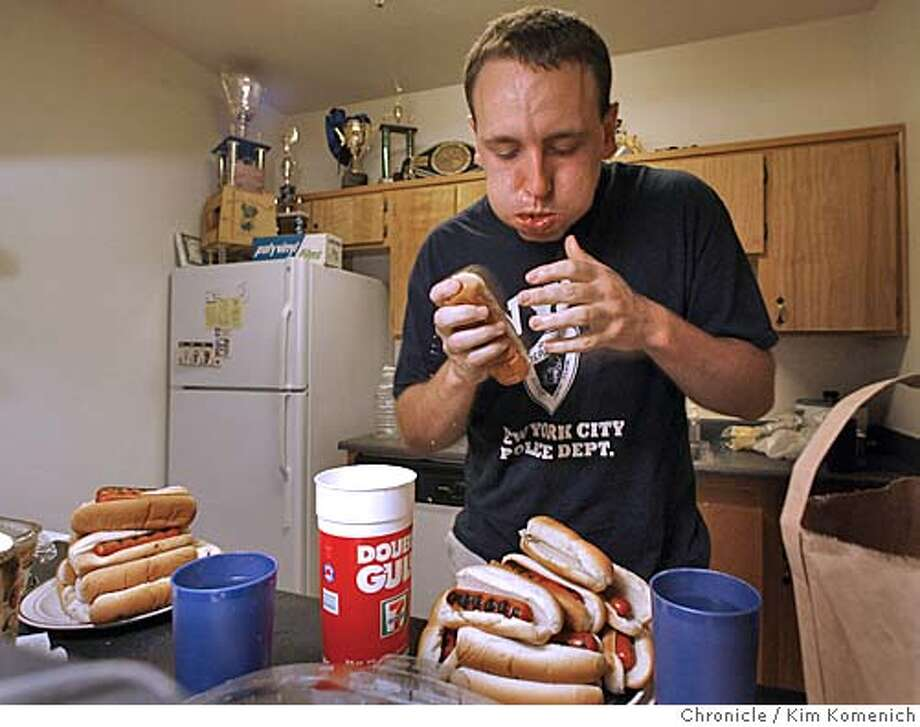 Joey Chestnut of San Jose downs 40 hot dogs in his San Jose apartment May 24 as he trains for the July 4 Nathan's hot dog eating competition in New York. He dunks the buns in the drink cup before he eats them. (NOTE: in the background are trophies from other speedeating contests, including the large trophy on the refrigerator from the Stockton asparagus eating contest. Kim Komenich / The Chronicle  **Joey Chestnut MANDATORY CREDIT FOR PHOTOG AND SAN FRANCISCO CHRONICLE/ -MAGS OUT Photo: Kim Komenich