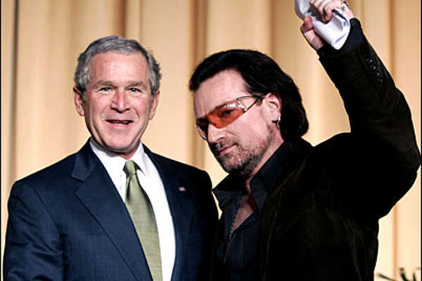 U.S. President George W. Bush stands with Irish rock star Bono after Bono spoke at the National Prayer Breakfast in Washington, February 2, 2006. Bush addressed the audience following Bono's remarks. REUTERS/Kevin Lamarque