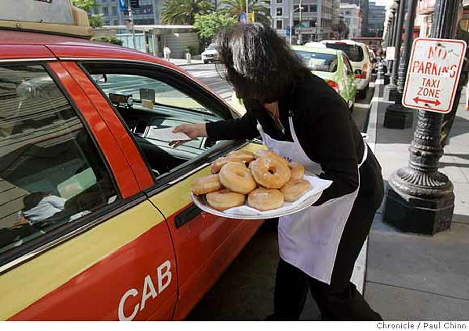 Sandy Yi-Davis serves donuts to cab drivers during Taxi Drivers Appreciation Day at the Westin St. Francis hotel in San Francisco, Calif. on Thursday, June 14, 2007. Cab drivers were treated to glazed donuts and coffee and entered a contest for a two night stay and dinner at the hotel.  PAUL CHINN/The Chronicle  **Sandy Yi-Davis Photo: PAUL CHINN