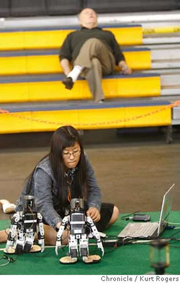 Soo-Mi Yang of England ready's her robots for competition as some one sitting in the stand catches up on their sleep.  The largest open robot competition kicks off at Fort Mason Festival Pavilion in San Francisco. FRIDAY, JUNE 15, 2007 KURT ROGERS SAN FRANCISCO SFC  THE CHRONICLE ROBOGAMES_0095_kr.jpg MANDATORY CREDIT FOR PHOTOG AND SF CHRONICLE / NO SALES-MAGS OUT Photo: KURT ROGERS