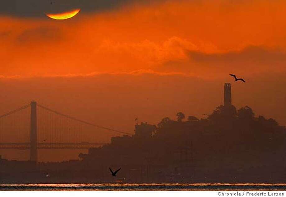 {object name} The sunrise finally broke through dense morning cloud cover over the Bay Bridge lighting up Coit Tower and southern tower of the Bay Bridge. The early morning photograph was taken at Fort Baker fishing pier under the Golden Gate at surise 7:30am this morning shot with a Canon EOS-1D Mark II N, 500mm lens, ISO: 640, my aperture was f/16, shutter speed: 1/500 of a second, the camera was programed for shutter priority. 1/26/06  Frederic Larson Photo: Frederic Larson