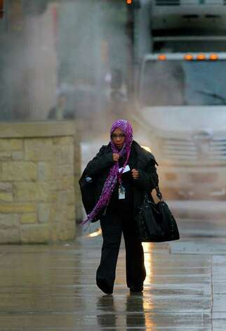 Valerie Lozano makes her way past some early morning mist on East Commerce street Monday February 13, 2012. Lozano was on her way to work at Rivercenter Mall. Photo: JOHN DAVENPORT, SAN ANTONIO EXPRESS-NEWS / SAN ANTONIO EXPRESS-NEWS (Photo may be sold to the public)