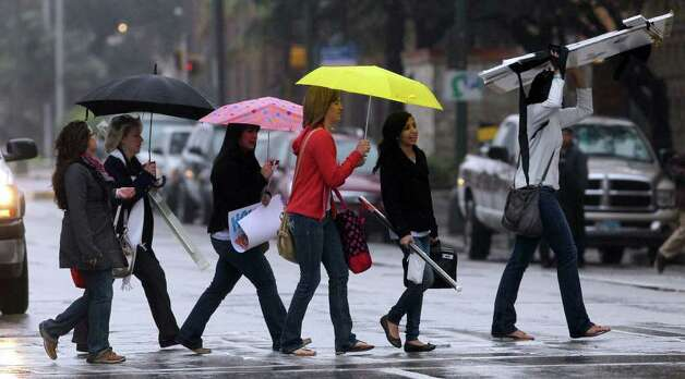 Pedestrians cross East Commerce street in the early morning drizzle Monday February 13, 2012 near Rivercenter Mall. Tuesday's forecast calls for partly cloudy skies with a high of 74 degrees. Photo: JOHN DAVENPORT, SAN ANTONIO EXPRESS-NEWS / SAN ANTONIO EXPRESS-NEWS (Photo may be sold to the public)
