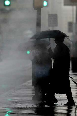 Pedestrians with umbrellas make their way past a steamy grate on East Commerce street early Monday morning near Rivercenter Mall. Tuesday's forecast calls for partly cloudy skies with a high of 74 degrees. Photo: JOHN DAVENPORT, SAN ANTONIO EXPRESS-NEWS / SAN ANTONIO EXPRESS-NEWS (Photo may be sold to the public)
