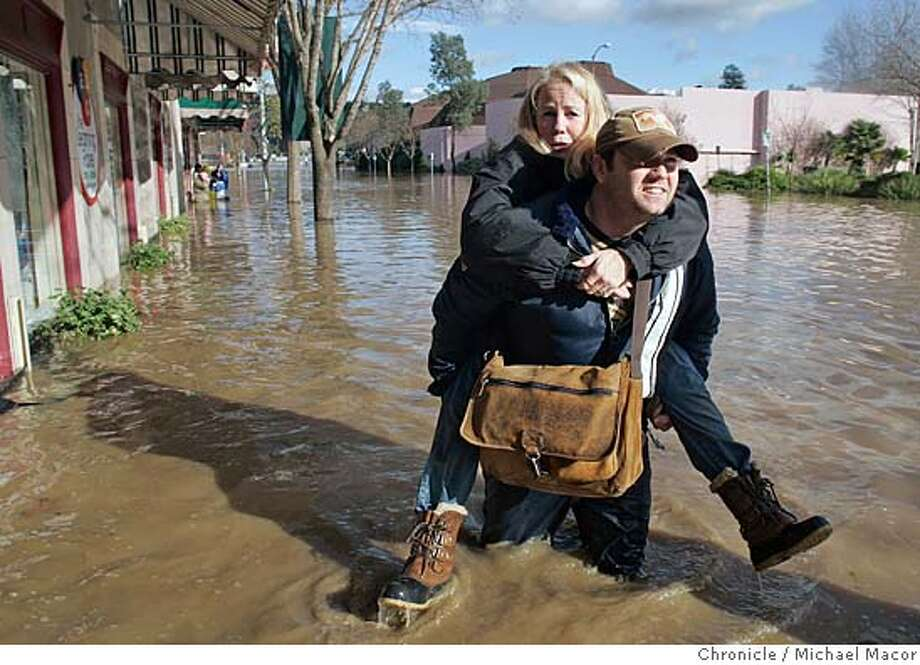 Sandy Nugent of Napa, Ca. is carried to saftey by her son Scott, affter they checked on the condition of their downtown business. About 3 feet of water filled the downtown Napa Valley Dance Center, which they have owned for the past 18 years. The Bay Area woke this morning to major flooding in several neighborhoods throughout the Bay Area. Event in Napa, Ca on 12/31/05. Photo by: Michael Macor / San Francisco Chronicle Photo: Michael Macor