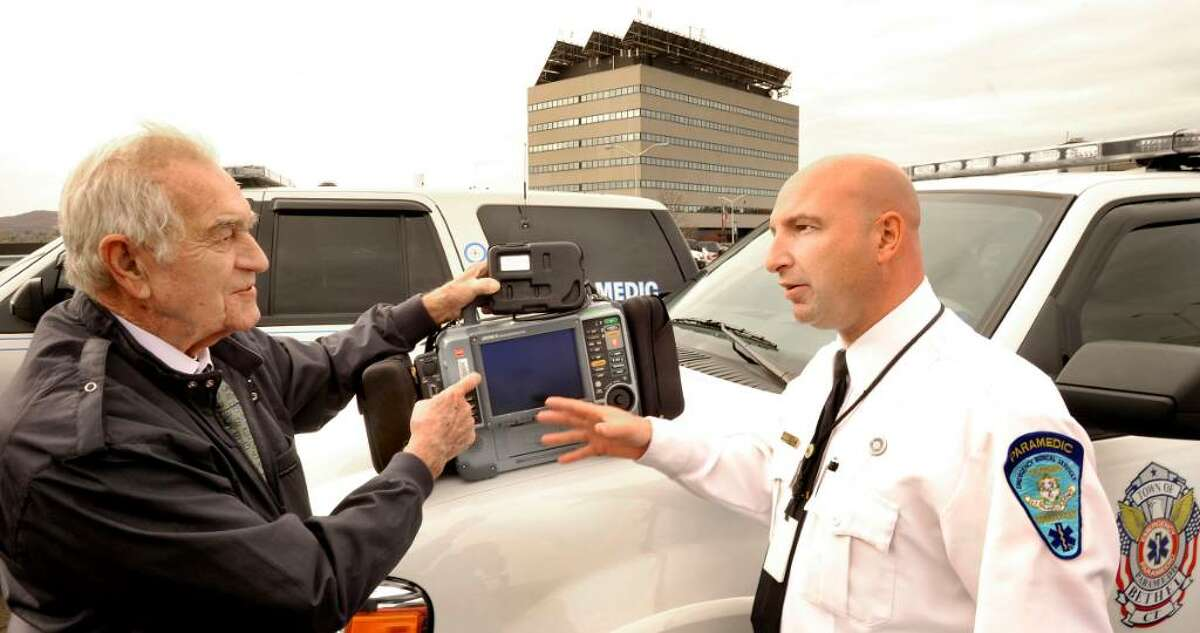 Bud Hawley, left, talks about the Lifepak-15 W/modem that he donated to Danbury Hospital, with Matt Cassavechia, Director of Emergency Medical Services, at the Heliport of Danbury Hospital, on Monday, Nov.2,2009.