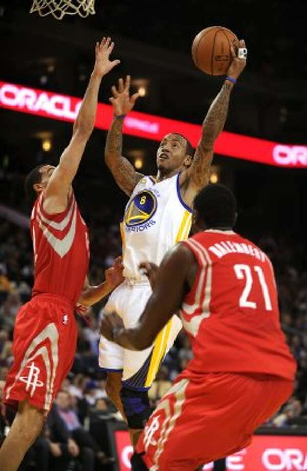 Feb. 12: Warriors 106, Rockets 97 Golden State's Monta Ellis, center, tries to score against Rockets guard Kevin Martin, left, and center Samuel Dalembert in the first quarter. Ellis torched the Rockets' defense for a game-high 33 points on 13-of-23 shooting, adding seven assists, five rebounds and two steals. Record: 16-12. (SUSAN TRIPP POLLARD / McClatchy-Tribune News Service)