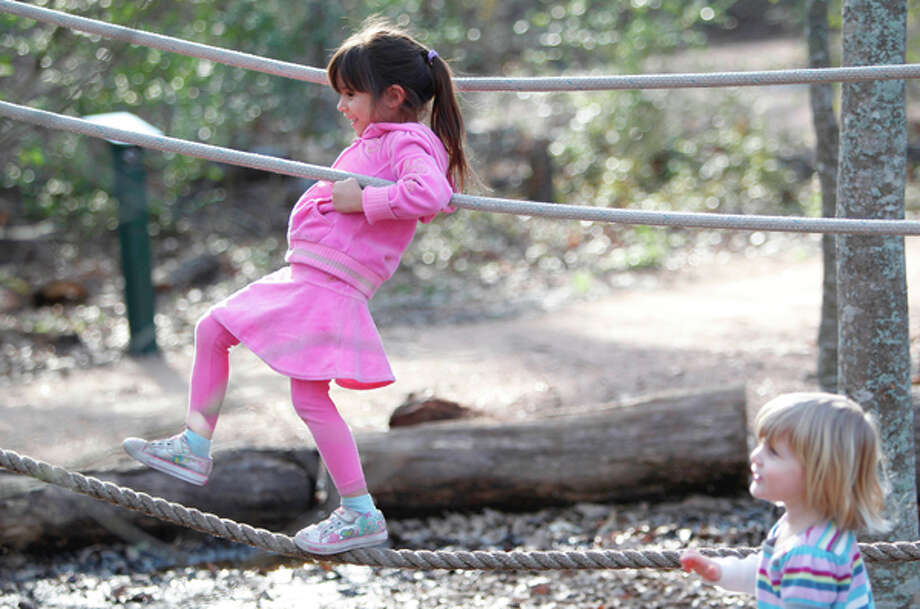 Gabriela Zapata, 4, balances on the tight rope in the children's playground at Houston Arboretum Nature Center on Tuesday, Feb. 7, 2012, in Houston. Sun broke through the clouds for a while in the afternoon. (Mayra Beltran / Houston Chronicle)