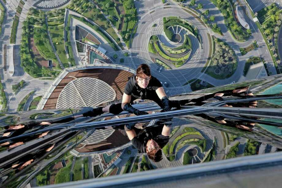 "Ethan Hunt (Tom Cruise) scales the outside of Dubai's Burj Khalifa in a scene from ""Mission Impossible-Ghost Protocol."" Photo: Contributed Photo"